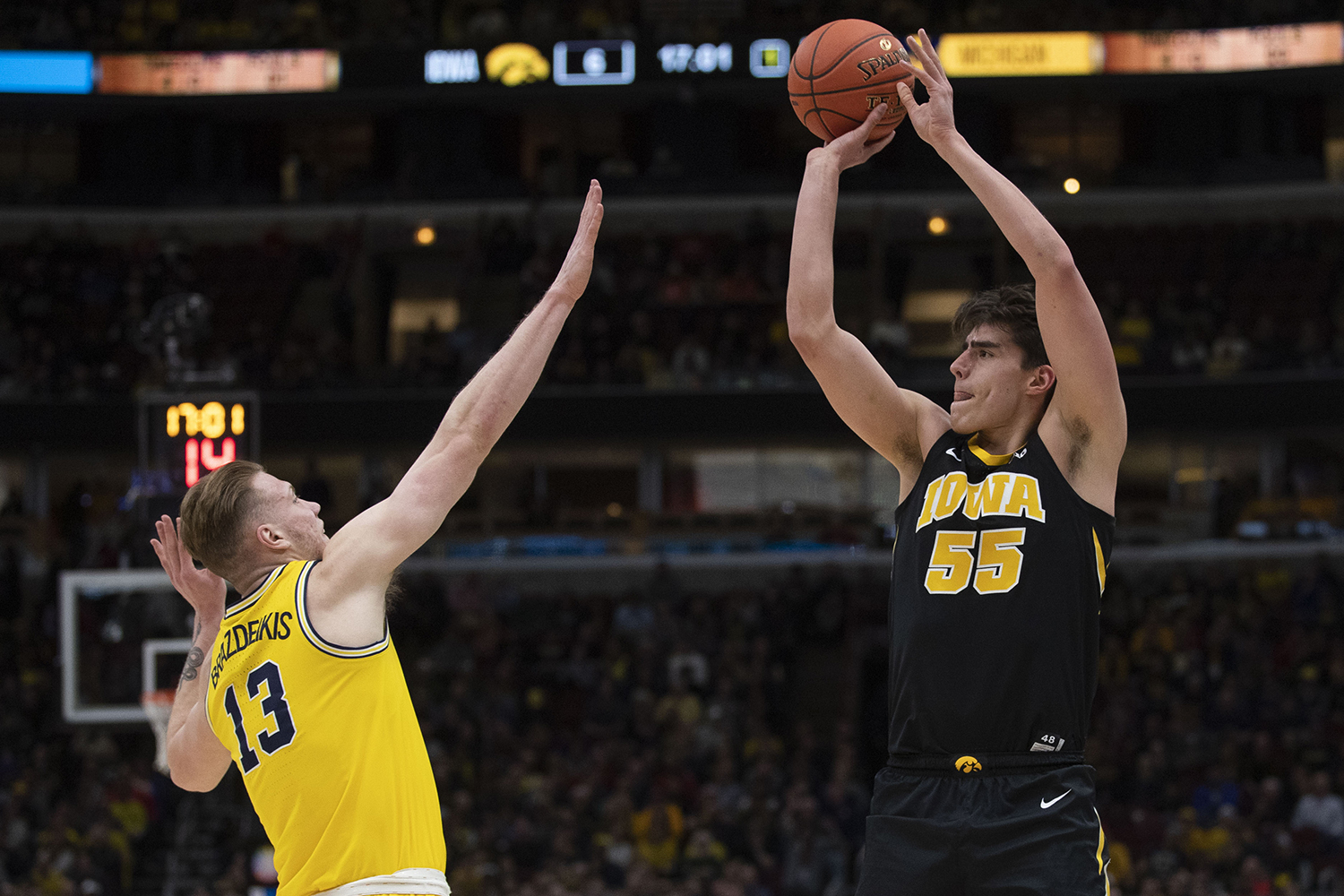 Iowa forward Luka Garza attempts a shot over Michigan forward Ignas Bradzeikis during the Iowa/Michigan Big Ten Tournament men's basketball game in the United Center in Chicago on Friday, March 15, 2019. The Wolverines lead the Hawkeyes, 40-27, at the half.