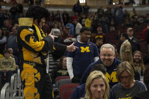Hawkeye Elvis gestures toward a Michigan fan during the Iowa/Michigan Big Ten Tournament men