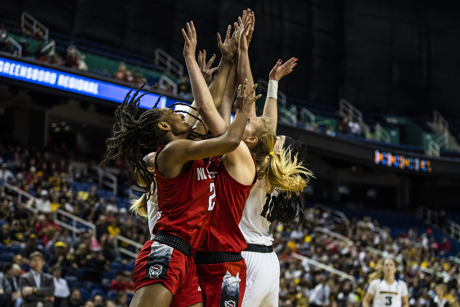 Iowa and NC State players reach for a rebound during the NCAA Sweet 16 game against NC State at the Greensboro Coliseum Complex on Saturday, March 30, 2019. The Hawkeyes defeated the Wolfpack 79-61.