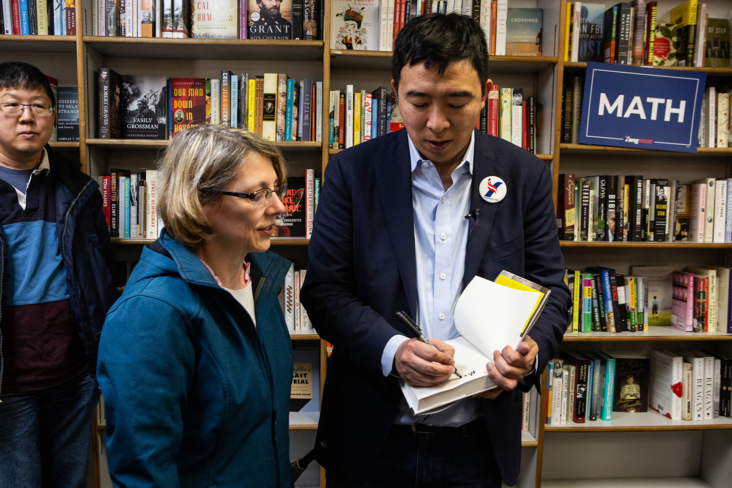 Democratic presidential hopeful Andrew Yang signs an attendee's copy of his book