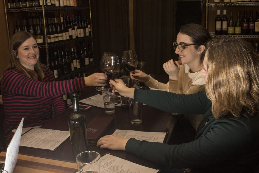 Graduate students (from left) Anna Williams, Laura Hayes and Lydia Maunz sit down for a drink in Brix Cheese Shop and Wine Bar on March 25, 2019. All three began as a reading group and have since continued to lean on each other for support through writing their dissertations. (Katie Goodale/The Daily Iowan)