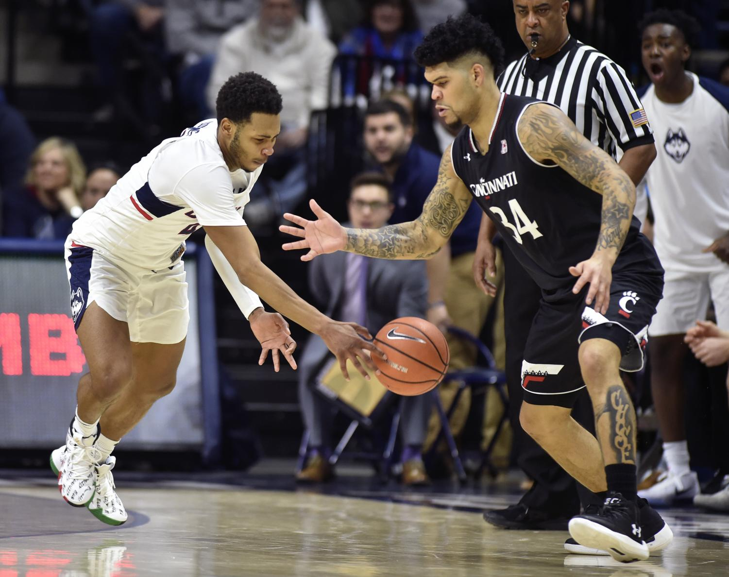 Connecticut's Jalen Adams (4) steals the ball from Cincinnati's Jarron Cumberland (34) at Gampel Pavilion in Storrs, Conn., on Saturday, Feb. 3, 2018. The visiting Bearcats won, 65-57.
