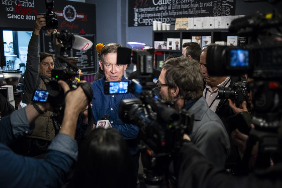 Former Colorado Gov. John Hickenlooper answers questions from the media during a campaign stop at the 392 Caffé in Clinton, Iowa on Saturday, March 9, 2019.
