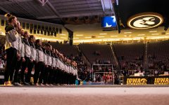 Iowa gymnasts stand for the nationan anthem during a women's gymnastics meet between Iowa and Iowa State at Carver-Hawkeye Arena on Friday, March 1, 2019. The Hawkeyes, celebrating senior night, fell to the Cyclones, 196.275-196.250.