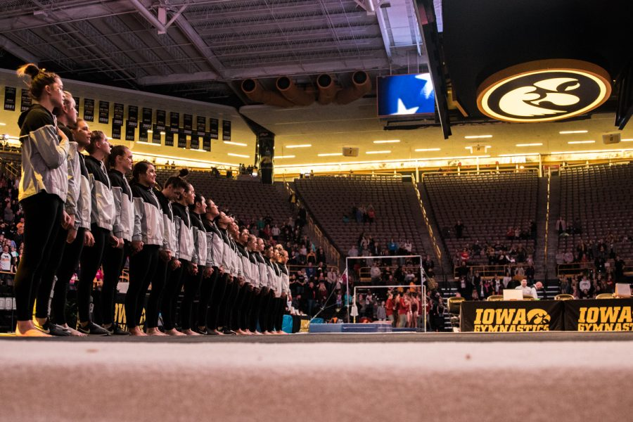 Iowa gymnasts stand for the nationan anthem during a women