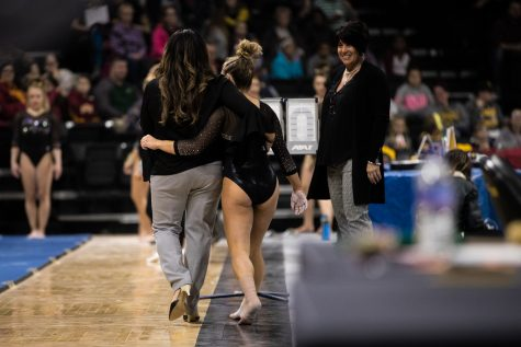 Iowa's Alex Greenwald walks with head coach Larissa Libby during a women's gymnastics meet between Iowa and Iowa State at Carver-Hawkeye Arena on Friday, March 1, 2019. The Hawkeyes, celebrating senior night, fell to the Cyclones, 196.275-196.250.