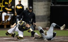 Iowa catcher Austin Martin tags out  Milwaukee catcher Tyler Bordner during the baseball game against Milwaukee at Duane Banks Field on Tuesday, April 23, 2019. The Hawkeyes defeated the Panthers 5-4.