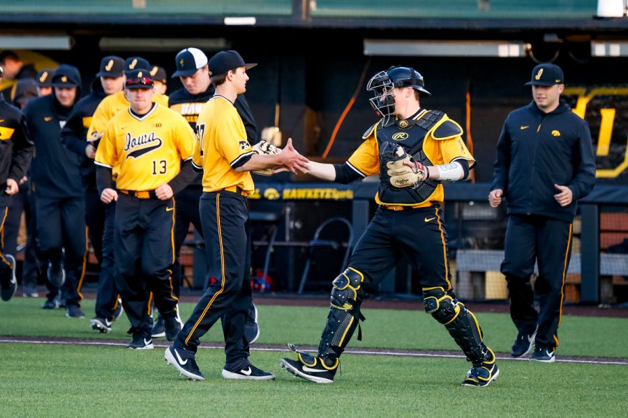 Iowa pitcher Jason Foster is congratulated by catcher Austin Mettica after a baseball game against Clarke University on Tuesday, Apr. 2, 2019. The Hawkeyes defeated the Pride 3-2.
