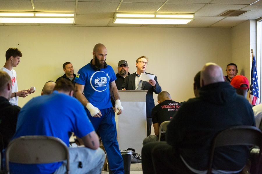 Fighters, corners, and fight officials listen as ring announcer PJ Stoppelworth calls roll before Elite Fight League no. 4 at the Teamsters Union Hall in Cedar Rapids on Saturday, Apr. 13, 2019.