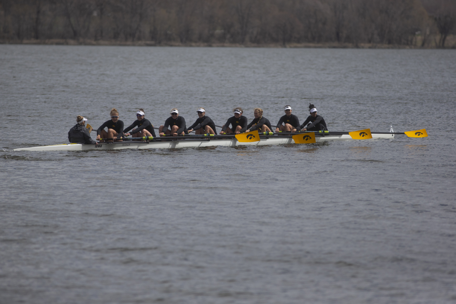 The Iowa varsity 8 crew looks to their supporters on the shore as they row back to the dock at the end of the first session of a women's rowing meet on Lake MacBride on Saturday April 13, 2019.