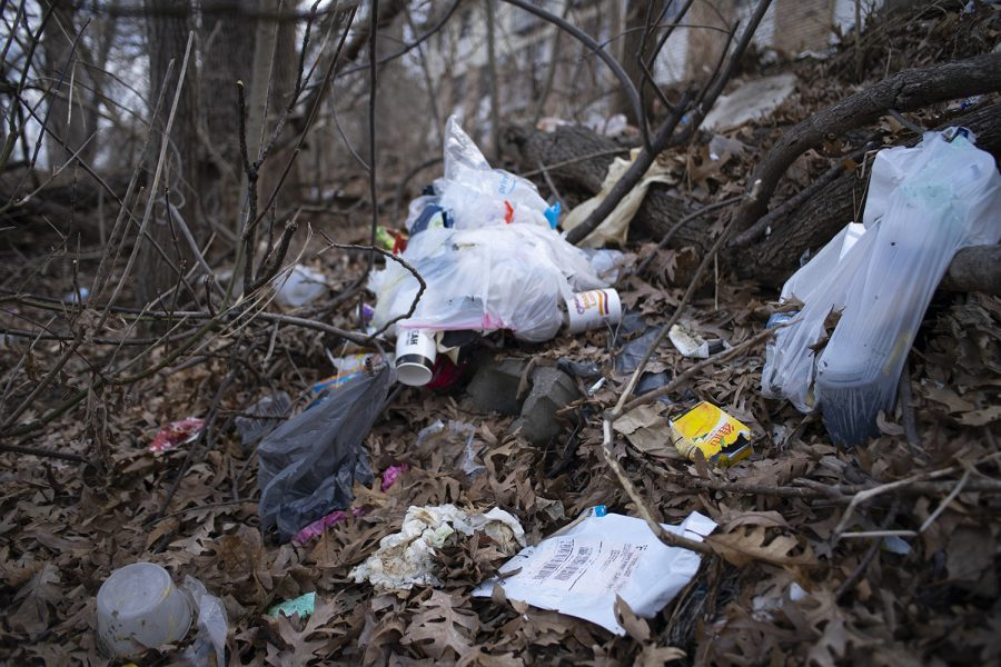 Litter is photographed on a hillside off of Riverside Drive near the theater building on Monday, March 25, 2019.