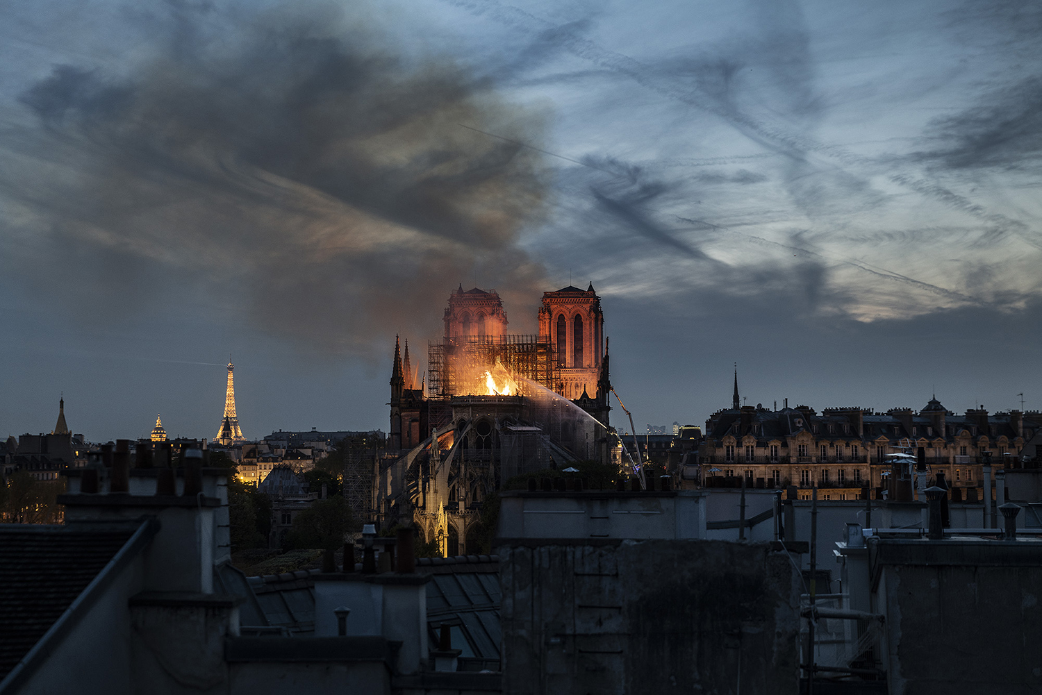 Smoke and flames rise from Notre-Dame Cathedral on April 15, 2019 in Paris, France. A fire broke out on Monday afternoon and quickly spread across the building, collapsing the spire. The cause is yet unknown but officials said it was possibly linked to ongoing renovation work.