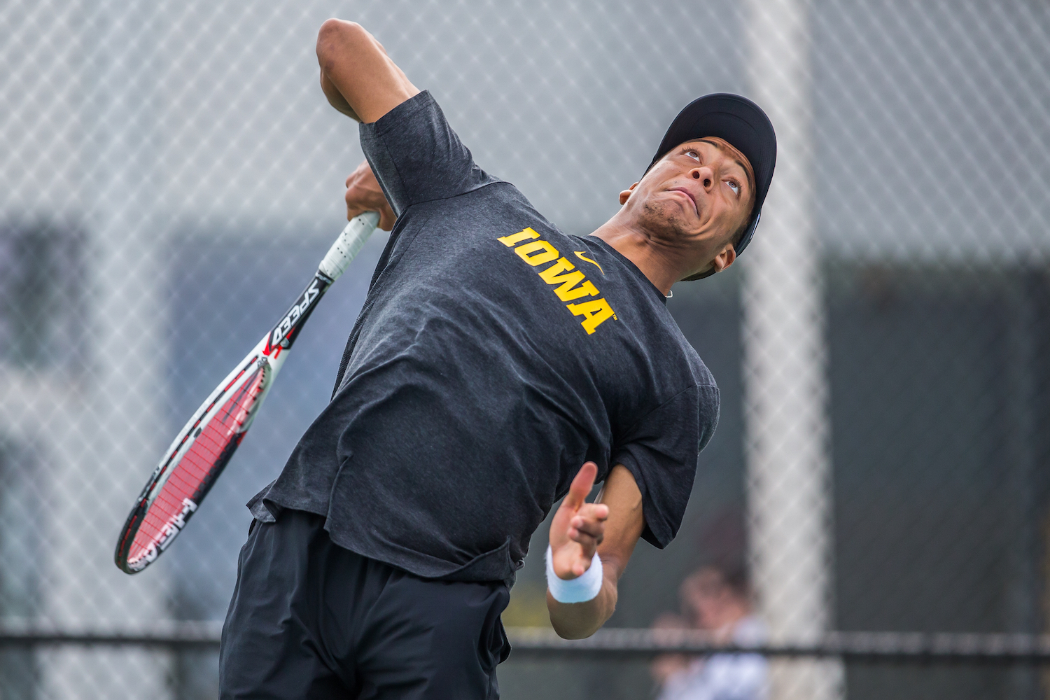 Iowa's Oliver Okonkwo hits a serve during a men's tennis match between Iowa and Ohio State at the HTRC on Sunday, April 7, 2019. The Buckeyes defeated the Hawkeyes, 4-1.