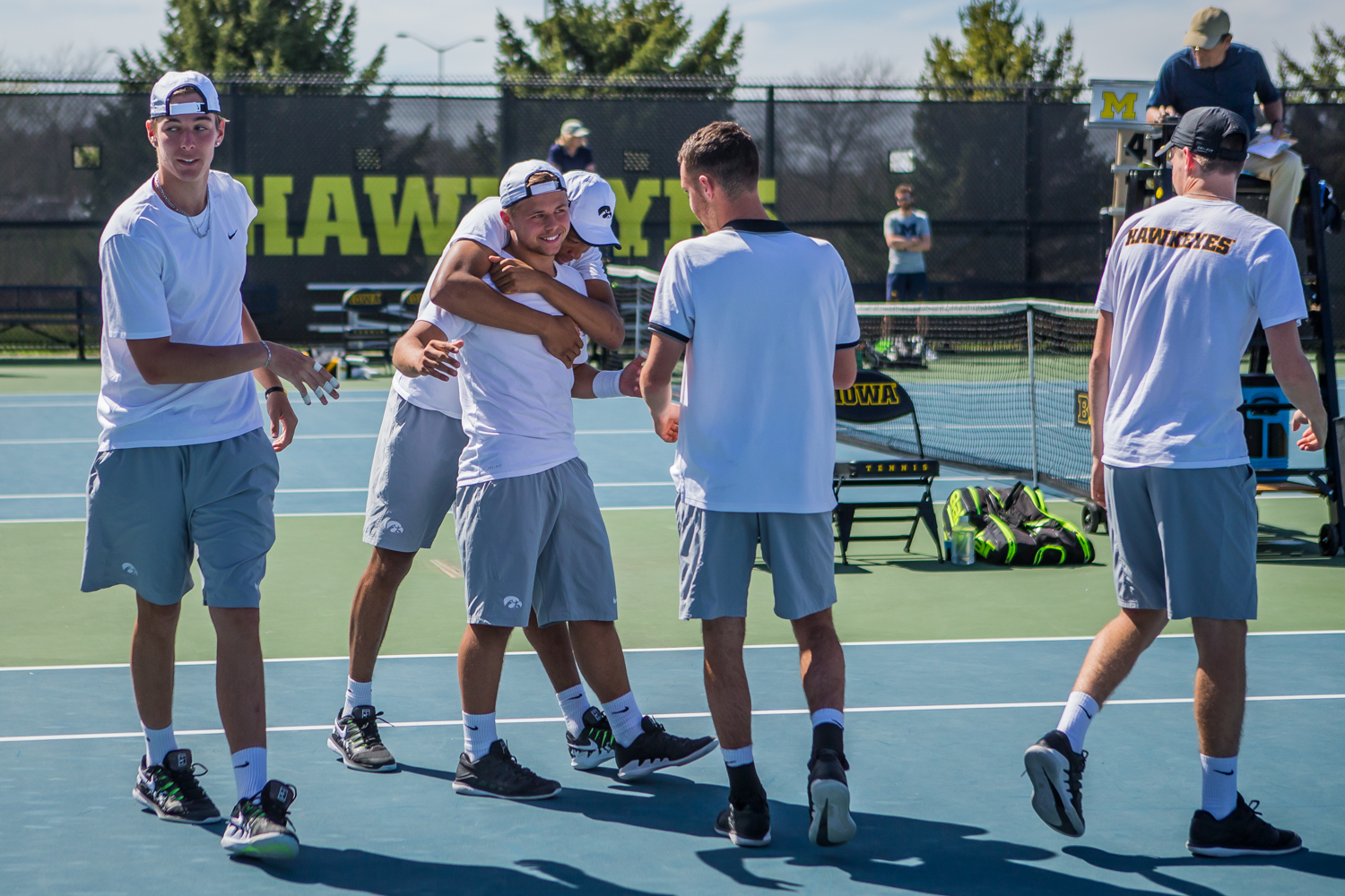 Iowa players huddle around Will Davies after his win during a men's tennis match between Iowa and Michigan at the HTRC on Sunday, April 21, 2019. The Hawkeyes, celebrating senior day, defeated the Wolverines, 4-1.