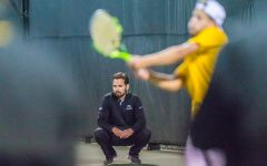 Iowa head coach Ross Wilson watches as Will Davies plays during a men's tennis match between Iowa and Michigan State at the HTRC on Friday, April 19, 2019. The Hawkeyes defeated the Spartans, 5-2.
