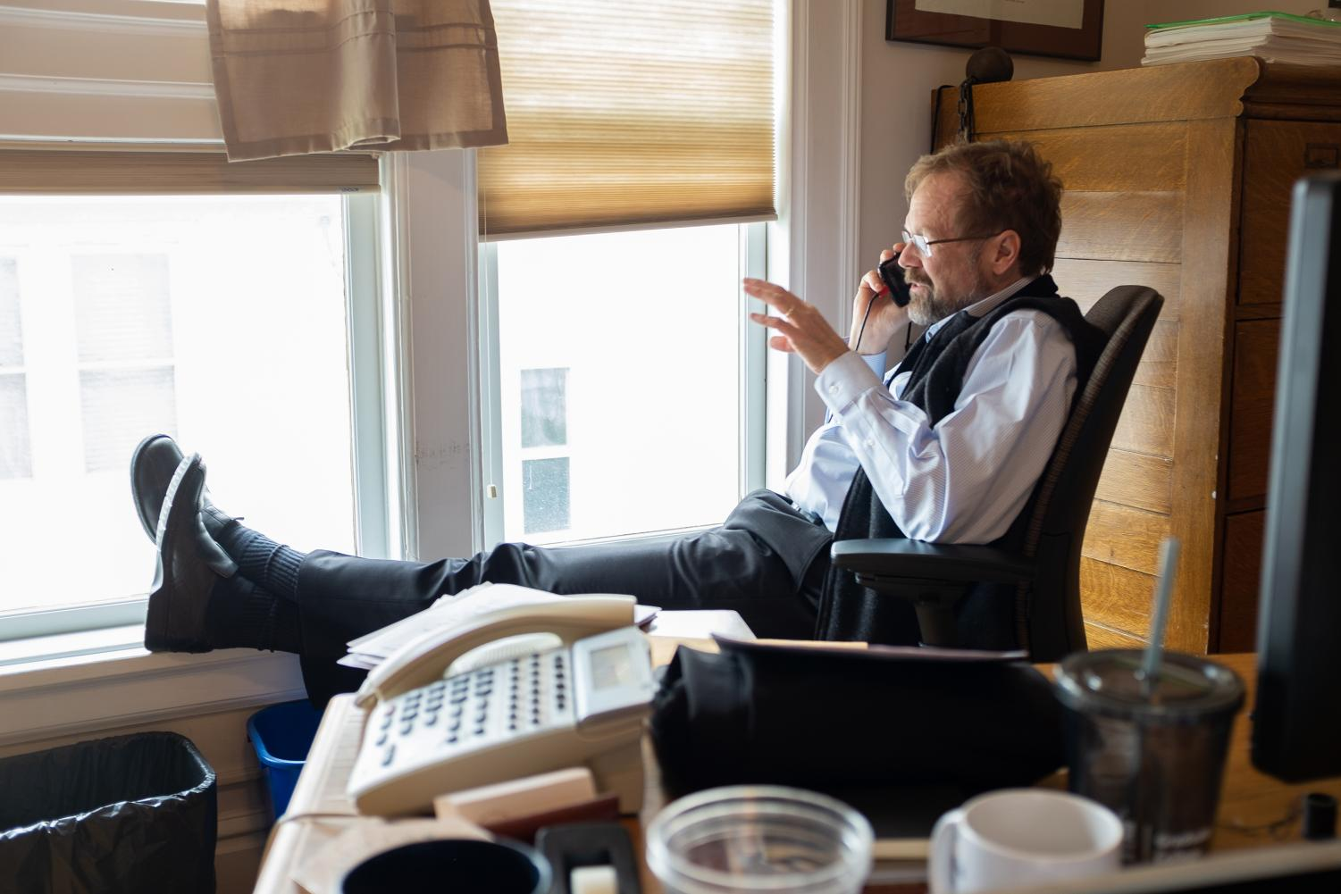 Christopher Merrill, the director of the International Writing Program, makes a phone call at his desk on April 12. Merrill's career began with covering the 1990 Fifa World Cup in Italy, and he has visited more than 100 countries.