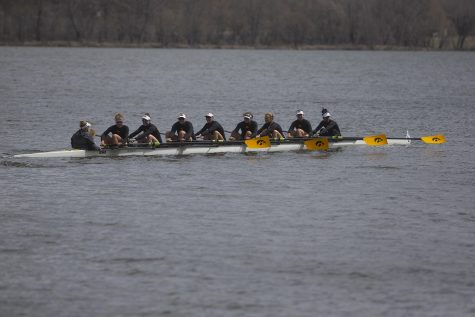 The Iowa varsity 8 crew looks to their supporters on the shore as they row back to the dock at the end of the first session of a women