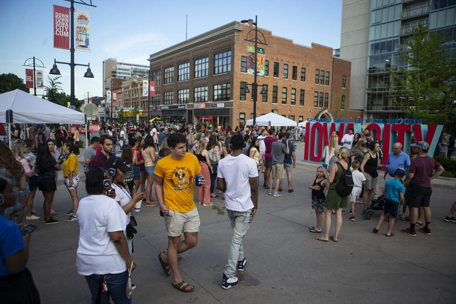 People+stand+by+the+Iowa+City+sign+during+Block+Party+in+downtown+Iowa+City+on+June+22%2C+2019.+Several+blocks+of+Iowa+City+were+reserved+for+games%2C+performances+and+vendors.+