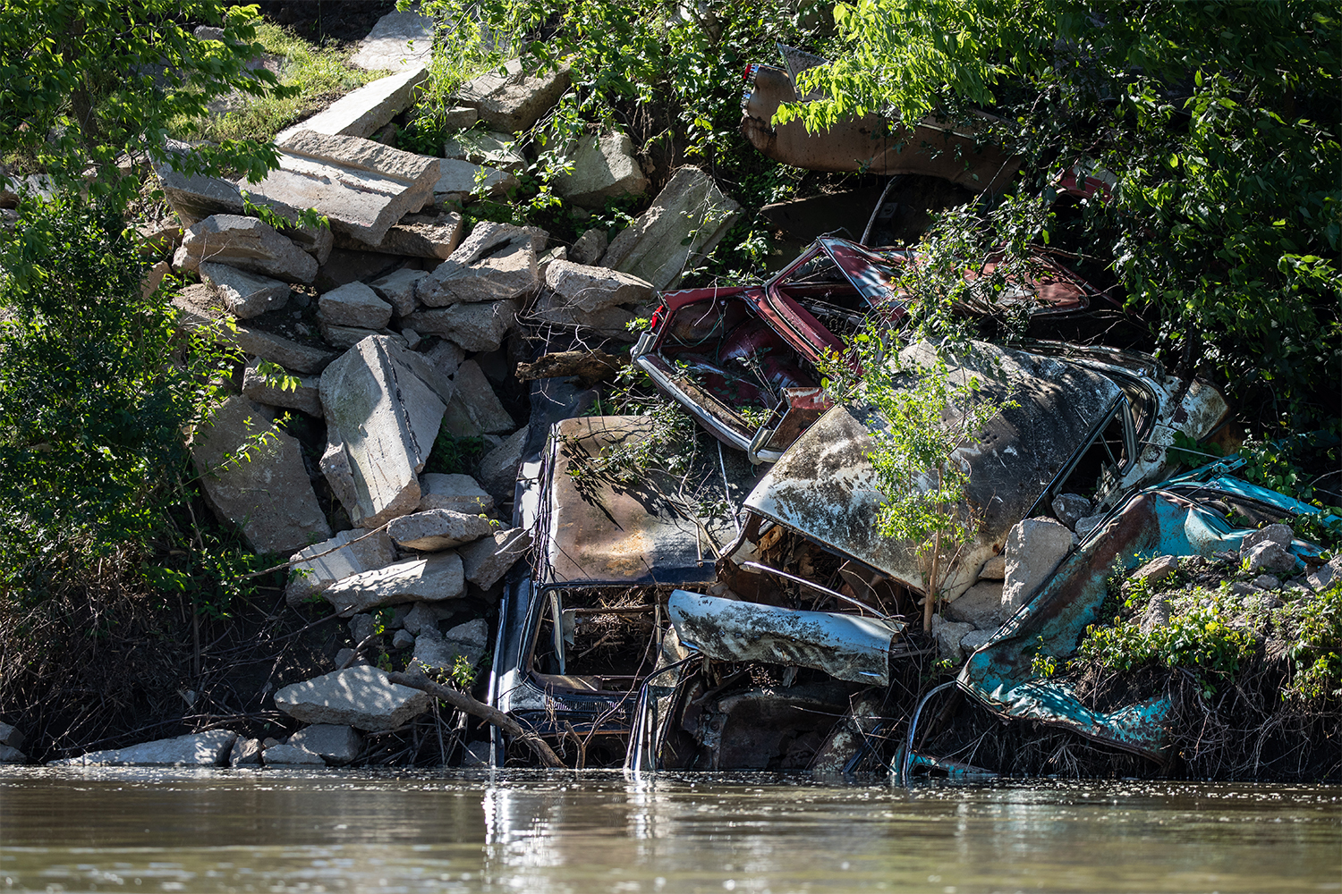 Vintage+vehicles+lay+embedded+into+the+riverbank+of+the+Iowa+River+south+of+Riverside%2C+Iowa+on+June+13%2C+2019.+In+efforts+to+reduce+riverbank+erosion%2C+vehicles+are+sometimes+placed+on+the+shore.