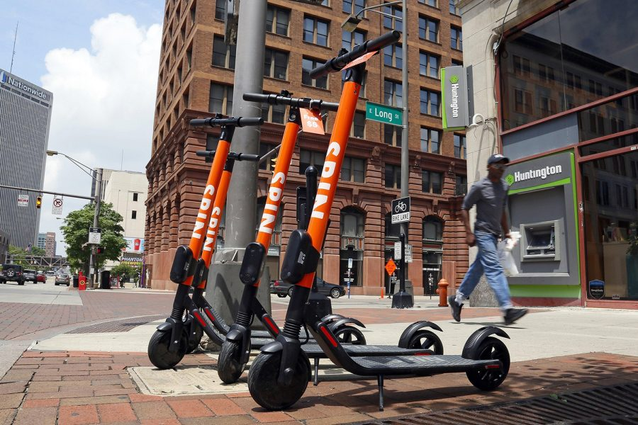 Spin scooters sit parked at the intersection of High and Gay streets in downtown Columbus. (Adam Cairns/Dispatch/TNS)