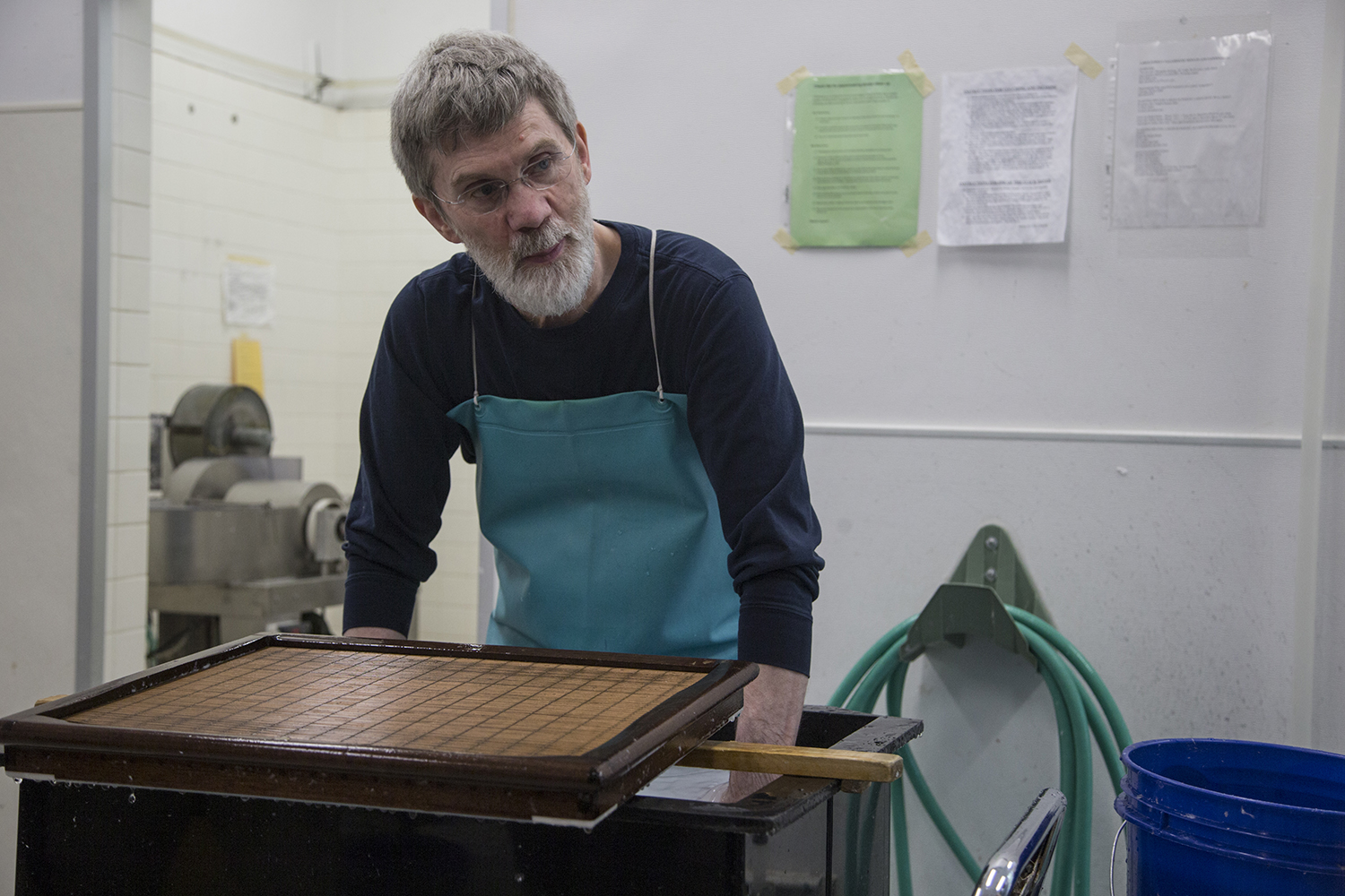 Director of The Center for the Book Timothy Barrett shifts paper pulp during a paper-making demonstration at the Center for the Book in North Hall on June 18, 2019. Graduate students were shown how to shift pulp to create sheets of paper. (Katie Goodale/The Daily Iowan)