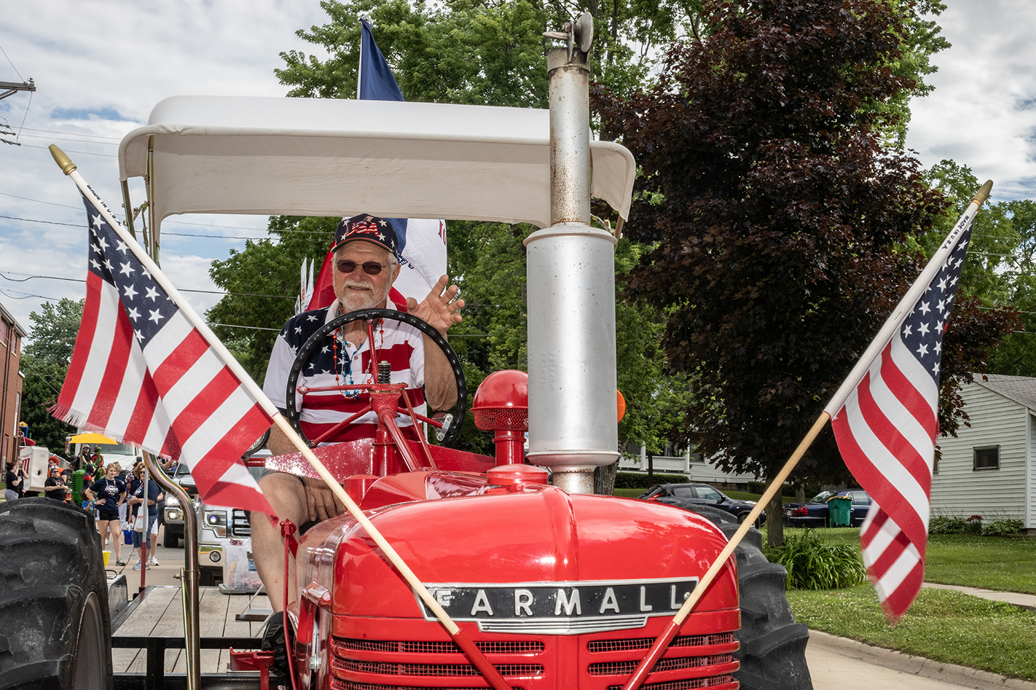Dick+Svoboda+waves+from+the+seat+of+his+Farmall+tractor+before+pulling+a+float+for+the+Buchanan+County+Republicans+for+the+annual+4th+of+July+parade+in+Independence%2C+Iowa.+This+is+the+159th+4th+of+July+parade+in+Independence.+