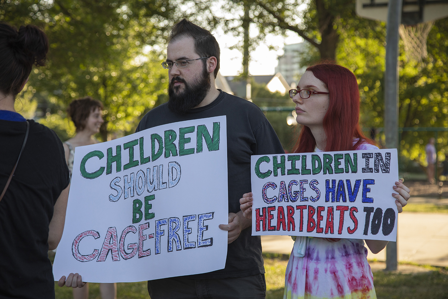 "Participants hold posters during the ""Lights for Liberty: Vigil to End Human Concentration Camps"" at College Green Park on Friday, July 12, 2019. (Tian Liu/The Daily Iowan)"