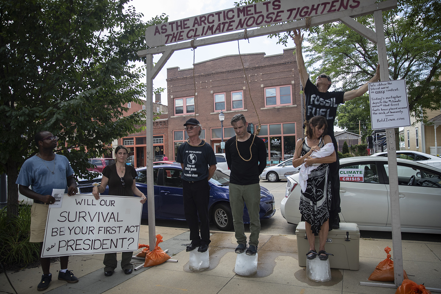 Demonstrators protest climate change action outside of the Progress Iowa Corn Feed in Newbo City Market in Cedar Rapids on July 14, 2019. 10 candidates came to meet supporters and give speeches. Demonstrators stood on a block of ice with nooses around their necks.