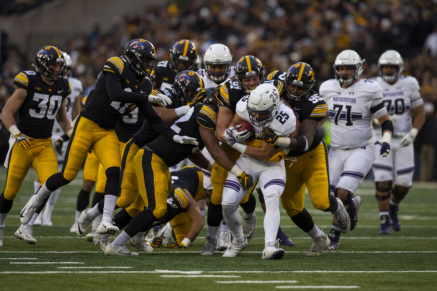 Northwestern running back Isaiah Bowser is tackled by Iowa defense during the Iowa/Northwestern football game at Kinnick Stadium on Saturday, November 10, 2018. The Wildcats defeated the Hawkeyes, 14-10. (Lily Smith/The Daily Iowan)