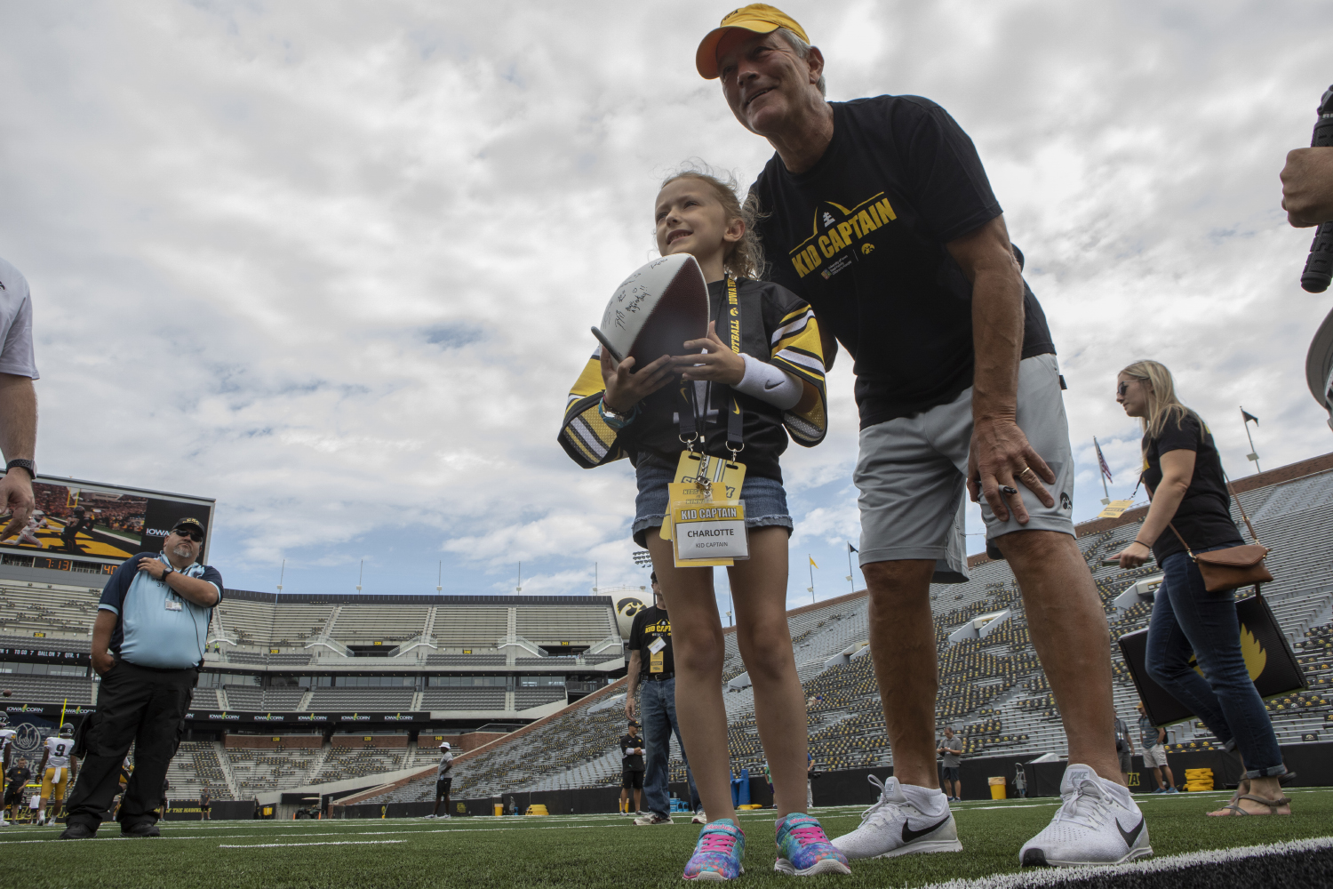 Kid Captain Charlotte Keller and Iowa football head coach Kirk Ferentz pose for a picture on Kinnick's field at Kids Day at Kinnick on Saturday, Aug. 10, 2019. Kids Day at Kinnick is an annual event for families to experience Iowa's football stadium, while watching preseason practice and honoring this year's Kid Captains.