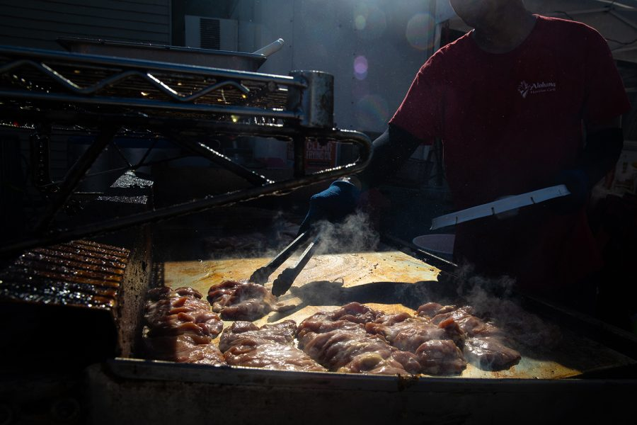 A chef for the Hawaiian Grill food vendor at the Hinterland Music Festival cooks some chicken on August 4, 2019 in Saint Charlies, Iowa