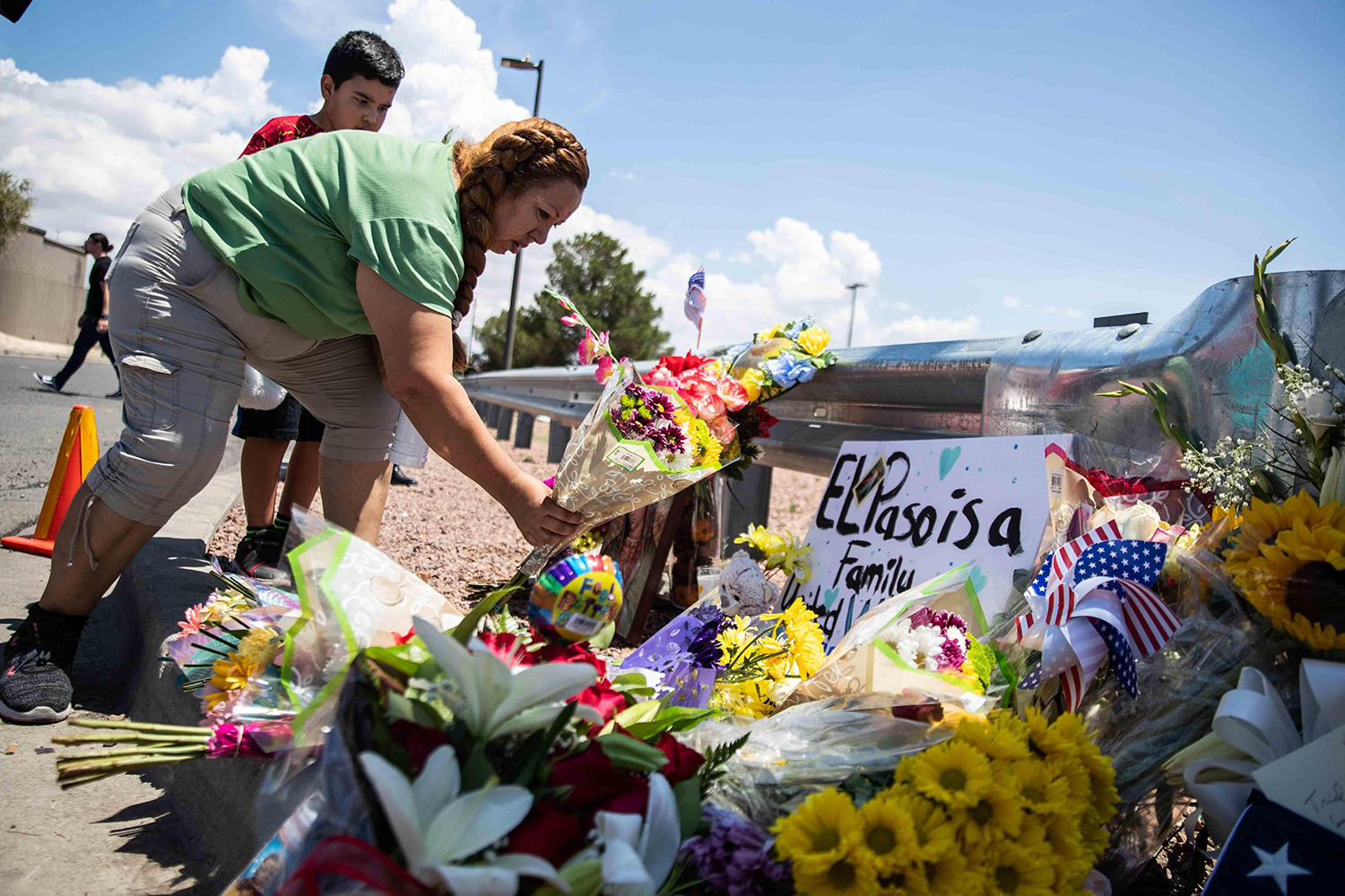 Carmen Roldan brings some flowers to honor the memory of the victims of the mass shooting occurred in Walmart on Saturday morning in El Paso on Sunday, August 4, 2019. [LOLA GOMEZ / AMERICAN-STATESMAN]