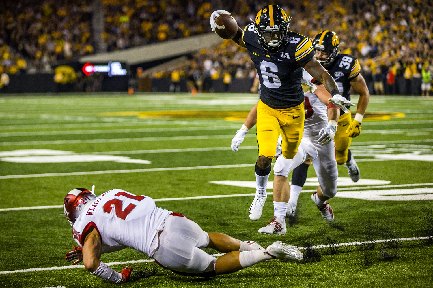 Iowa wide receiver Ihmir Smith-Marsette jumps over Miami (Ohio) defensive back Sterling Weatherford during the Iowa football game against Miami (Ohio) at Kinnick Stadium on Saturday, August 31, 2019. The Hawkeyes defeated the Redhawks 38-14.