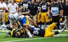 Iowa defenders converge on MTSU quarterback Asher O'Hara during a football game between Iowa and Middle Tennessee State at Kinnick Stadium on Saturday, September 28, 2019. The Hawkeyes defeated the Blue Raiders, 48-3.