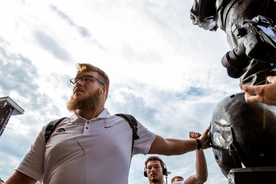 Iowa Football Landan Paulsen (68) touches a statue of Nile Kinnick as he walks into Kinnick Stadium in Iowa City, Iowa on September 7, 2019. The Hawkeyes defeated the Scarlet Knights 30-0.