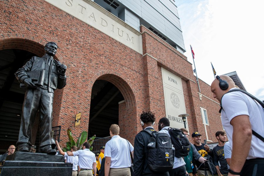 The Iowa football team walks in and touches a statue of Nile Kinnick as he walks into Kinnick Stadium in Iowa City, Iowa on September 7, 2019. The Hawkeyes defeated the Scarlet Knights 30-0.