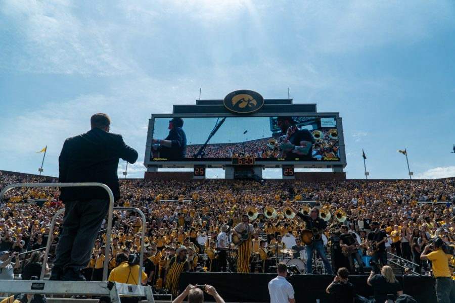A conductor directs several bands during a football game between Iowa and Rutgers at Kinnick Stadium on Saturday, September 7, 2019. The Hawkeyes defeated the Scarlet Knights 30-0. (Roman Slabach/ The Daily Iowan)