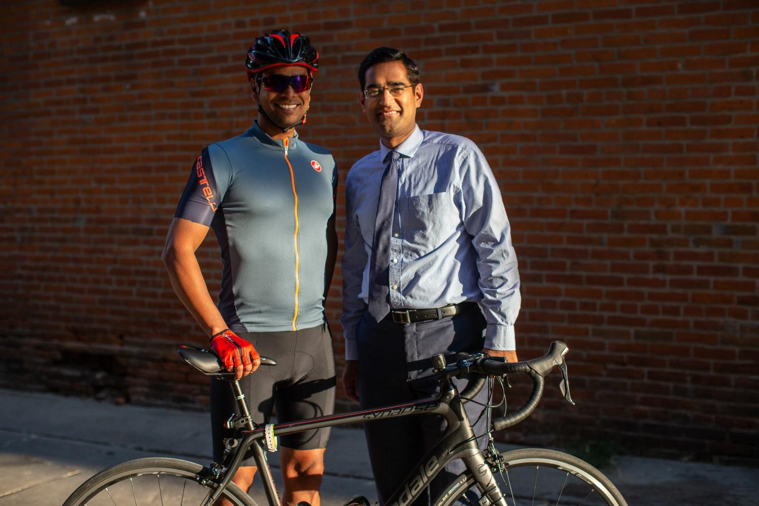Ashish Mishra and Varun Monga pose for a portrait in downtown Iowa City on Thursday. The pair met through cycling when Mitra biked 1,000 miles across Iowa to raise money for sarcoma.