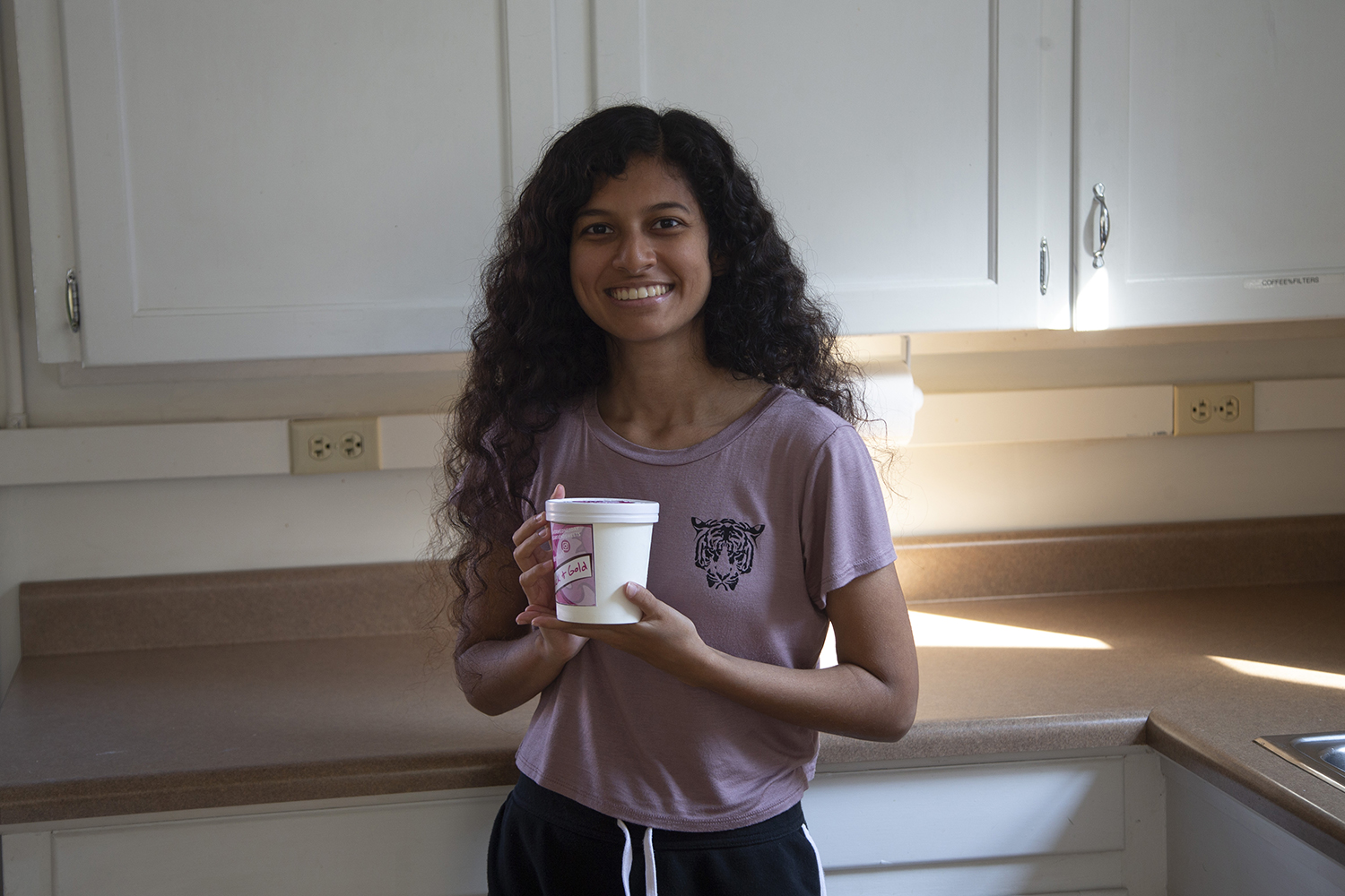 Sugar Fiend Sweets owner Ramya Kolusu poses for a portrait with a pint of her Black & Gold ice cream in the kitchen of the Bedell Entrepreneurship Learning Laboratory on Friday, Sept. 20, 2019. Kolusu is in her final semester at the University of Iowa and was inspired to start her own ice cream business by a now-closed ice cream shop in her hometown, Clinton, Iowa. She began making her own ice cream approximately three years ago after learning from videos online.