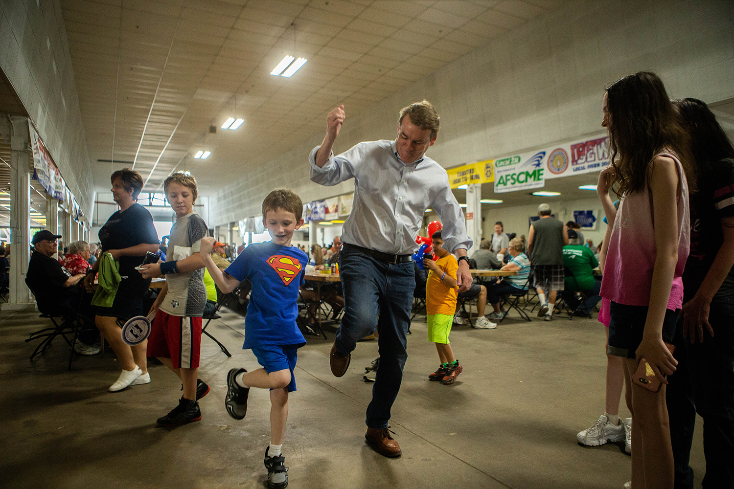 Liam Bogs (7) of Cedar Rapids teaches Sen. Michael Bennet, D-CO, during the Hawkeye Area Labor Council Picnic at Hawkeye Downs on Monday, September 2, 2019.