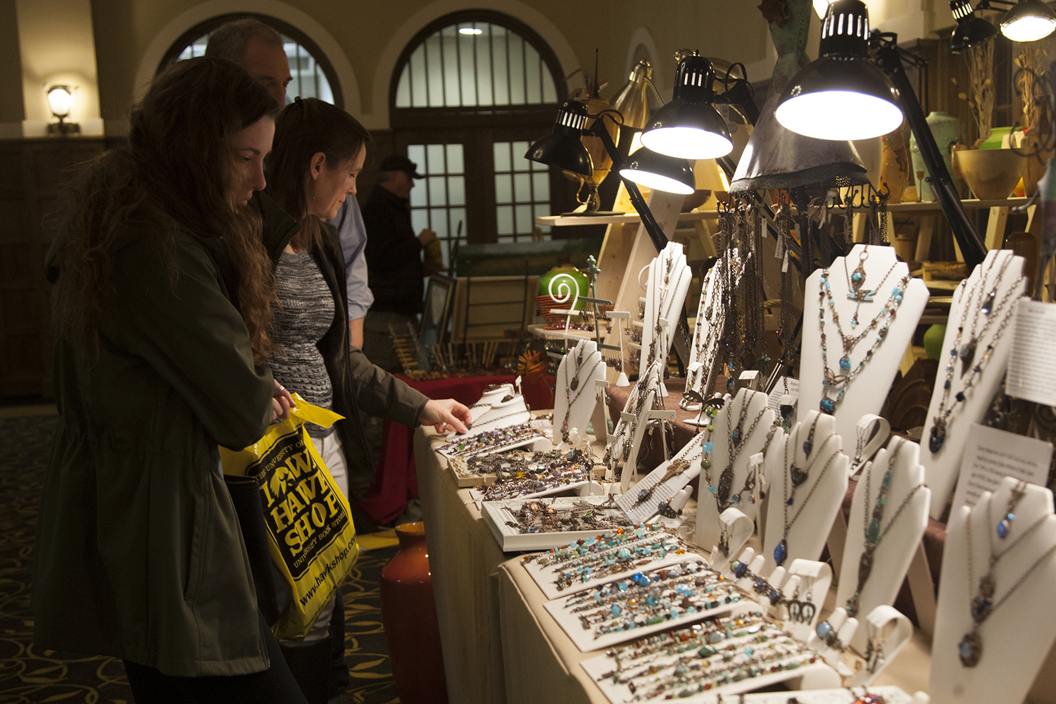 A family looks at jewelry during the Spring Art Expose in the IMU Main Lounge on Saturday Apr. 21, 2018. Put on by the UI Fine Arts Council, the Spring Art Expose celebrates local artists.