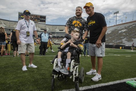 Kid Captain Cien Currie and his father pose for a picture Hawkeye Football Head Coach Kirk Ferentz at Kids Day at Kinnick on Saturday, August 10, 2019. Kids Day at Kinnick is an annual event for families to experience Iowa