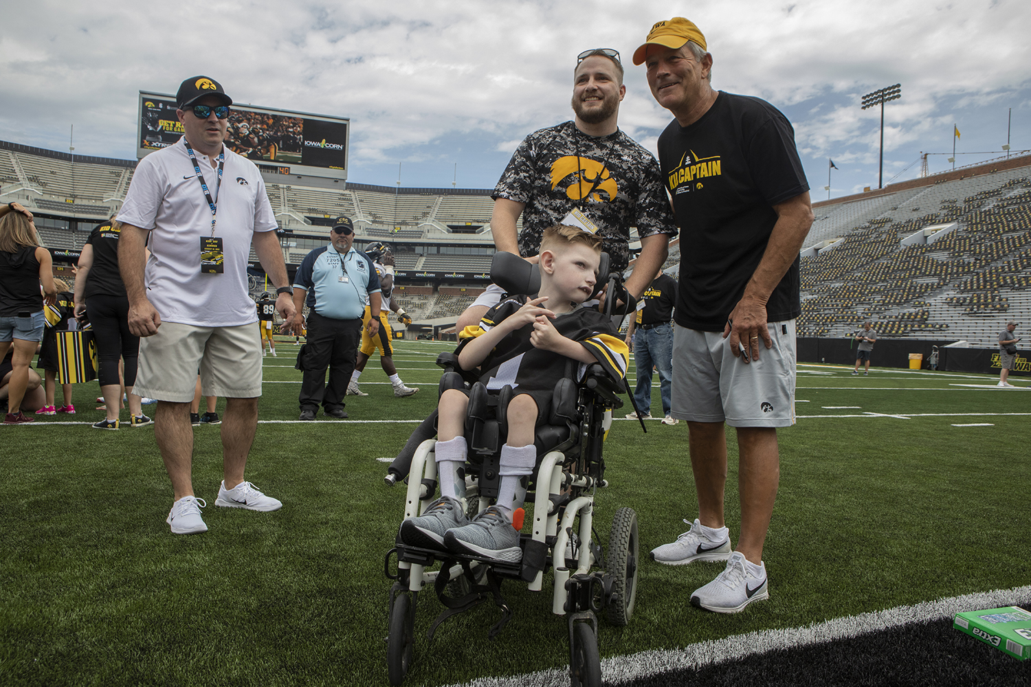 Kid Captain Cien Currie and his father pose for a picture Hawkeye Football Head Coach Kirk Ferentz at Kids Day at Kinnick on Saturday, August 10, 2019. Kids Day at Kinnick is an annual event for families to experience Iowa's football stadium, while watching preseason practice and honoring this year's Kid Captains.