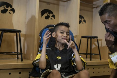Kid Captain Enzo Thongsoum poses for the camera in the Hawkeye football locker room at Kids Day at Kinnick on Saturday, August 10, 2019. Kids Day at Kinnick is an annual event for families to experience Iowa
