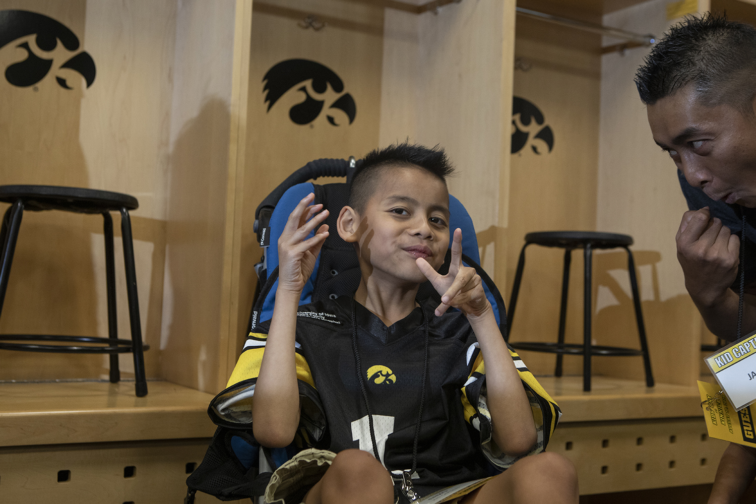 Kid Captain Enzo Thongsoum poses for the camera in the Hawkeye football locker room at Kids Day at Kinnick on Saturday, August 10, 2019. Kids Day at Kinnick is an annual event for families to experience Iowa's football stadium, while watching preseason practice and honoring this year's Kid Captains.