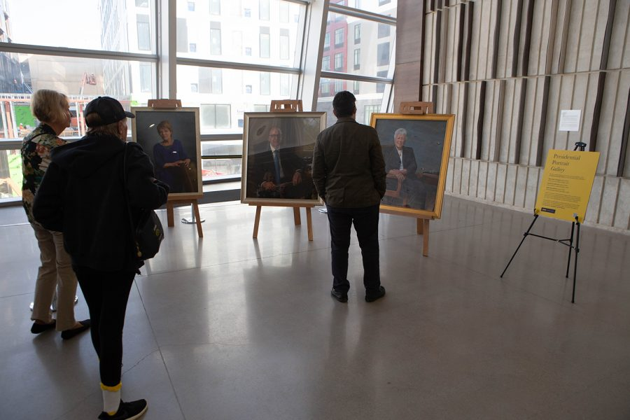 Community members look at the newest additions to the Presidential Portrait Gallery following a panel discussion by four former University of Iowa Presidents and current UI President Bruce Harreld on Friday, Oct. 18, 2019 in the Voxman concert hall. The event coincided with the unveiling of portraits of former UI Presidents Mary Sue Coleman, David Skorton, and Sally Mason, which will be on display on the fifth floor of the UI Main Library.