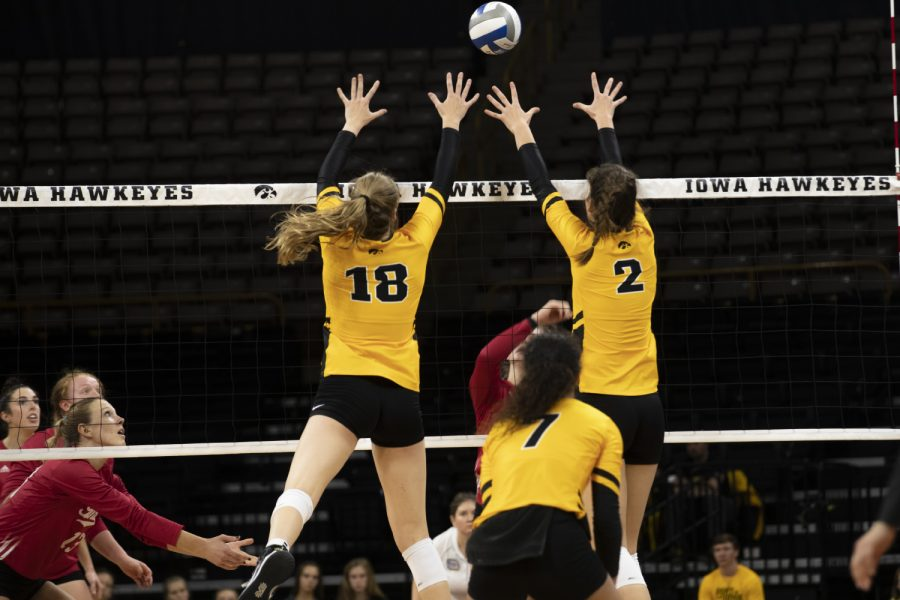 Iowa+middle+blocker+Hannah+Clayton+and+setter+Courtney+Buzzerio+reach+for+the+ball+during+the+Iowa+volleyball+game+against+Indiana+on+Sunday+Oct.+20+2019.+The+Hawkeyes+defeated+the+Hoosiers+3-1.