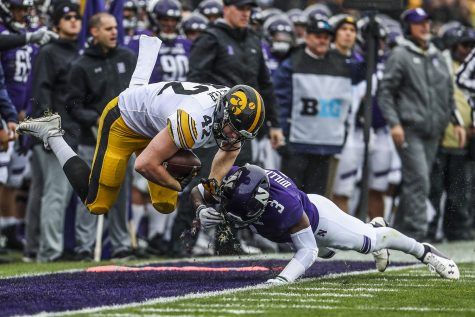Iowa tight end Shaun Beyer flies over Northwestern defensive back Trae Williams during the Iowa vs. Northwestern football game at Ryan Field on Saturday, October 26, 2019. The Hawkeyes defeated the Wildcats 20-0. Williams had one tackle during the game.