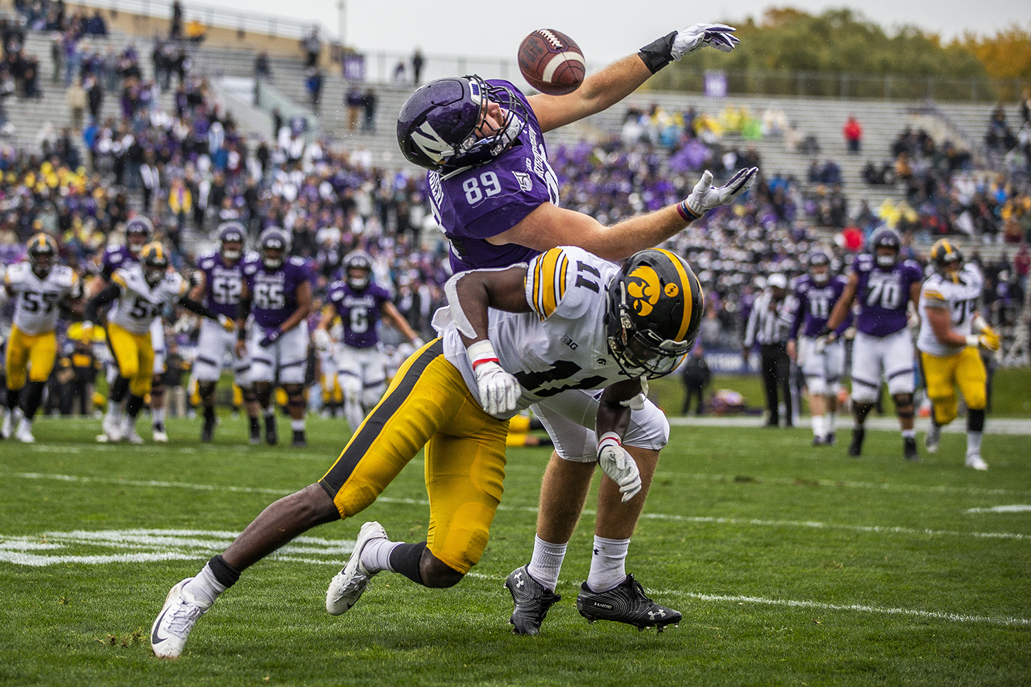 Northwestern slotback Charlie Mangieri loses the ball as Iowa defensive back Michael Ojemudia collides with him during the Iowa vs. Northwestern football game at Ryan Field on Saturday, October 26, 2019. The Hawkeyes defeated the Wildcats 20-0. Ojemudia had a total of three tackles during the game.