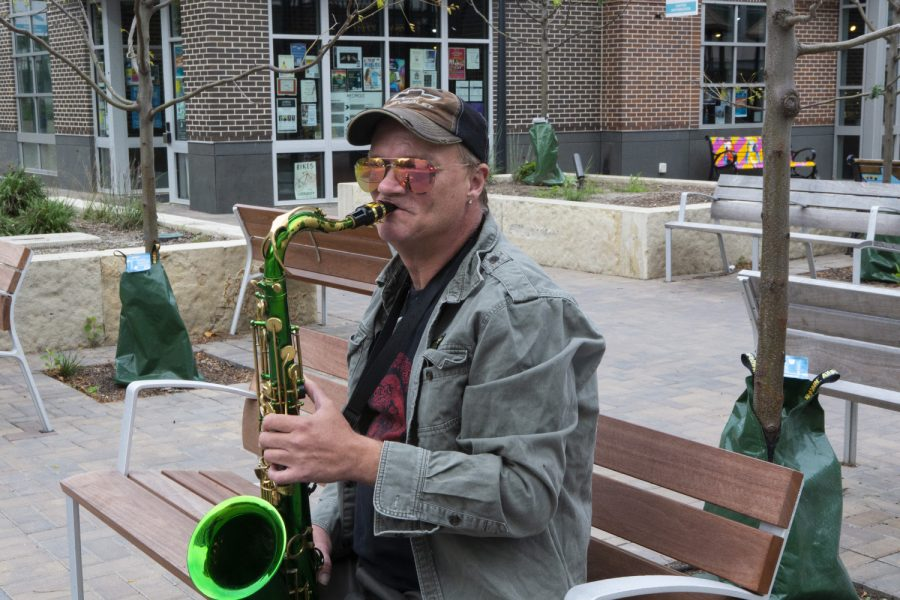 """Ed Raines playing his Saxophone in the Ped Mall On October 9, 2019. """"I just want to enjoy the last of the good weather while I can,"""" Raines said.  (Raquele Decker/The Daily Iowan.)"""